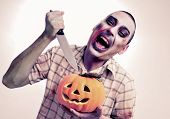 a scary zombie about to stick a knife into a carved pumpkin