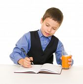 schoolboy drinks juice at a desk with diary and pen