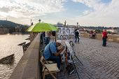 Cartoonist takes a break during his shift on Charles bridge, Prague