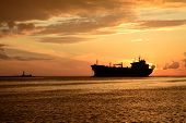 sunset at pier and a passing ship
