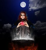 stock photo of witches cauldron  - Young witch with red potion and cauldron on night sky background - JPG