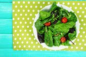 Fresh green salad in bowl on wooden table