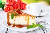 Cheese cake  in plate and tuft of roses on table on nature background