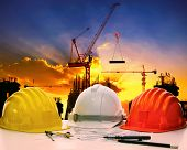 Safety Helmet On Civil Engineer Working Table Against Crane Lifting Meterial In Building Constructio