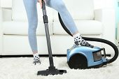 Girl vacuuming in room