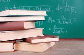 Books on wooden table on blackboard background