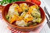Cabbage stuffed with sauerkraut in ceramic pan on board