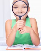 Girl Is Looking At Big Paper Using Magnifier