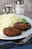 pic of mashed potatoes  - Two meat patties with mashed potato on a wooden table - JPG