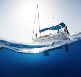 picture of bottomless  - Split shot of the sail boat on surface and its underwater view - JPG