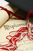 stock photo of graduation cap  - A diploma and grad hat represent a high achieving student - JPG