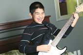 Asian boy play guitar in his bedroom