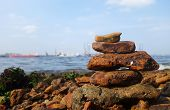 picture of shipyard  - Rocks on the coast of the sea with shipyard as background - JPG
