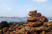 image of shipyard  - Rocks on the coast of the sea with shipyard as background - JPG