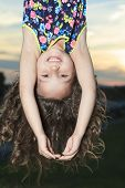 A upside down little girl at the sunset
