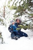 Mother And Baby Boy Playing In Snowy Winter Outdoor