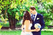 Toned photo of bride and groom outdoors park under trees