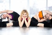 Group Of Three Females Doing Stretching Fitness Exercises In Class