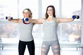 Team Of Sporty Young Females Having Intensive Aerobics Training With Dumbbells