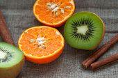 Fruit set - orange tangerine half,  kiwi and cinnamon sticks on hessian linen fabric cloth