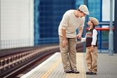 Young father and son on railway station platform
