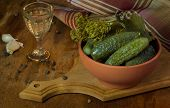 stock photo of vodka  - Pickles in a clay bowl and glass of vodka in the vintage on the wooden background - JPG