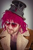 stock photo of lunate  - Pink haired bearded cool bum lunatic man - JPG