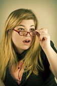 stock photo of dork  - Cute nerdy girl with reading glasses posing for a portrait