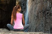 Young woman in pose sitting near waterfall
