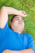 Stressful Fat Man Is Lying On The Green Grass With Arm On His Head