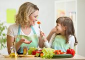kid girl and mother eating healthy food vegetables