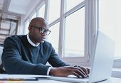 stock photo of handsome  - Image of african american businessman working on his laptop - JPG