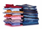 Stack Of Colorful Office Shirts And Jeans On A White Background