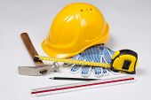 Close Up Of Builder's Work Tools And Yellow Helmet Over White