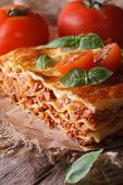 Italian Lasagna With Basil Close-up On Paper, Vertical Rustic