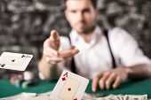 foto of only mature adults  - Young confident gangster man in shirt and suspenders is throwing his cards on poker table while he - JPG
