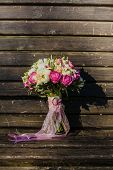 Wedding bouquet with a pink ribbon on wood surface