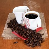 Cup of coffee with saucer, milk jug and coffe beans on the table