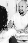 Tattoo Artist Attending To A Customer.