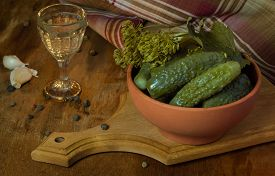 picture of vodka  - Pickles in a clay bowl and glass of vodka in the vintage on the wooden background - JPG