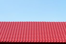 foto of red roof  - Red roof from a metal tile on a blue sky background - JPG