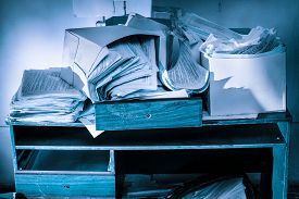 foto of messy  - Messy workplace with table and stack of paper - JPG