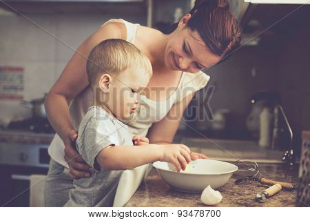 Mom with her 2 years old child cooking holiday pie in the kitchen to Mothers day, casual lifestyle p
