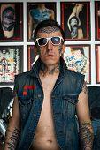 picture of vest  - Tattoo master in denim vest and white sunglasses in his studio - JPG