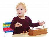 image of montessori school  - Very little girl in the history of the kindergarten is studying montessori materials - JPG