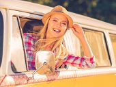 stock photo of recreational vehicles  - Cheerful young woman smiling at camera while looking through the vehicle window - JPG