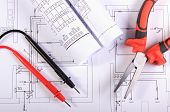 stock photo of electrical engineering  - Rolls of electrical diagrams cables of multimeter and metal pliers lying on construction drawings of house electrical drawings and tools for engineer jobs - JPG