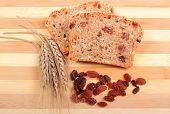 picture of fresh slice bread  - Slice of fresh baked wholemeal bread ears of wheat and heap of raisins lying on cutting board concept for healthy eating - JPG