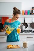 pic of oats  - A healthy woman listening to music is looking down pouring herself a freshly-made smoothie in which she has put vitamin-packed seasonal fruits nuts and oats. ** Note: Shallow depth of field - JPG