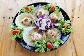 picture of scallops  - Baked Scallops with Cheese in black dish on wood table - JPG